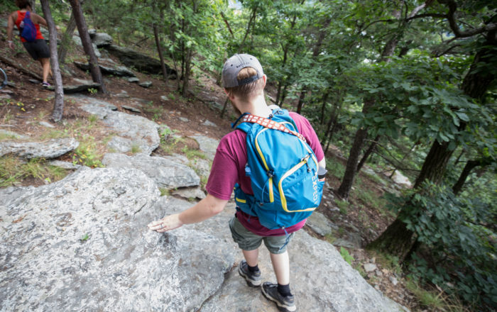Male hiker wearing daypack while walking on rocky shelf in Pennsylvania forest