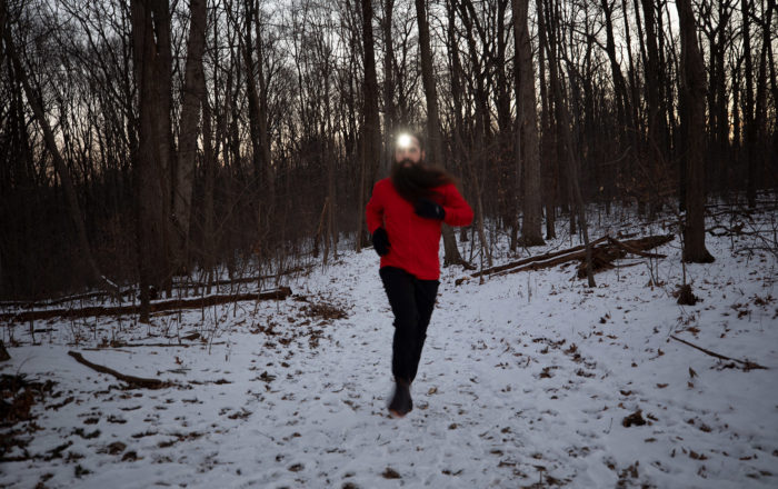 Steven running on wooded, snowy trail with headlamp