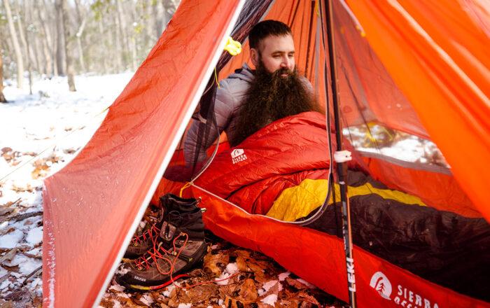 Steven in Sierra Designs sleeping bag inside Sierra Designs tent on snowy day