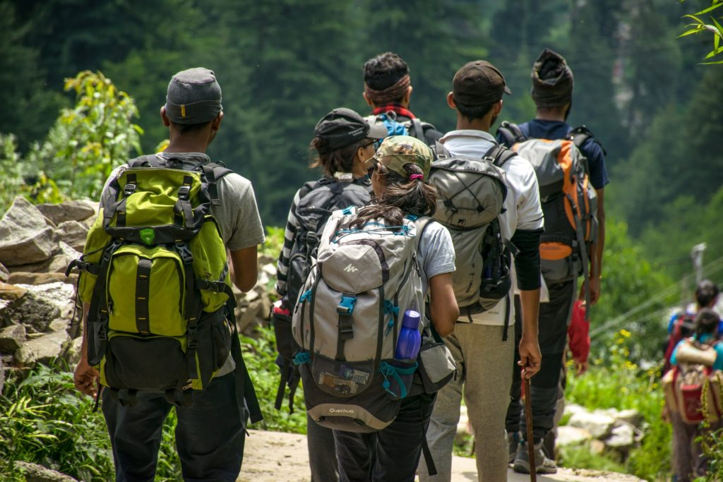 Group of men and women hiking on trail with backpacks