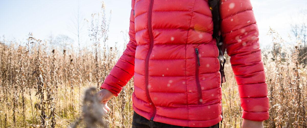 Woman in field wearing pink down jacket