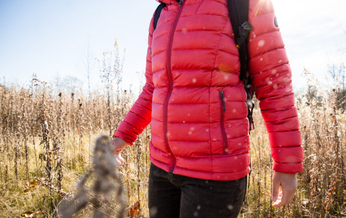 Woman in field wearing pink down jacket