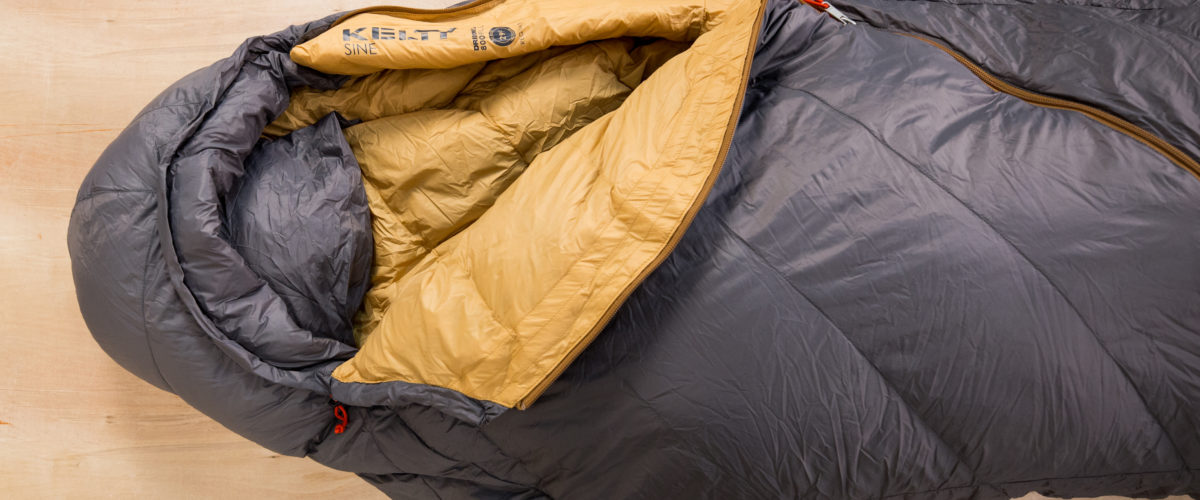 Partially unzipped Kelty Sine sleeping bag on wooden surface