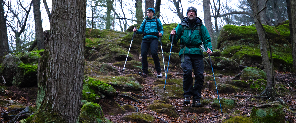 Becky and Troy using LEKI trekking poles to hike downhill among lichen-covered rocks