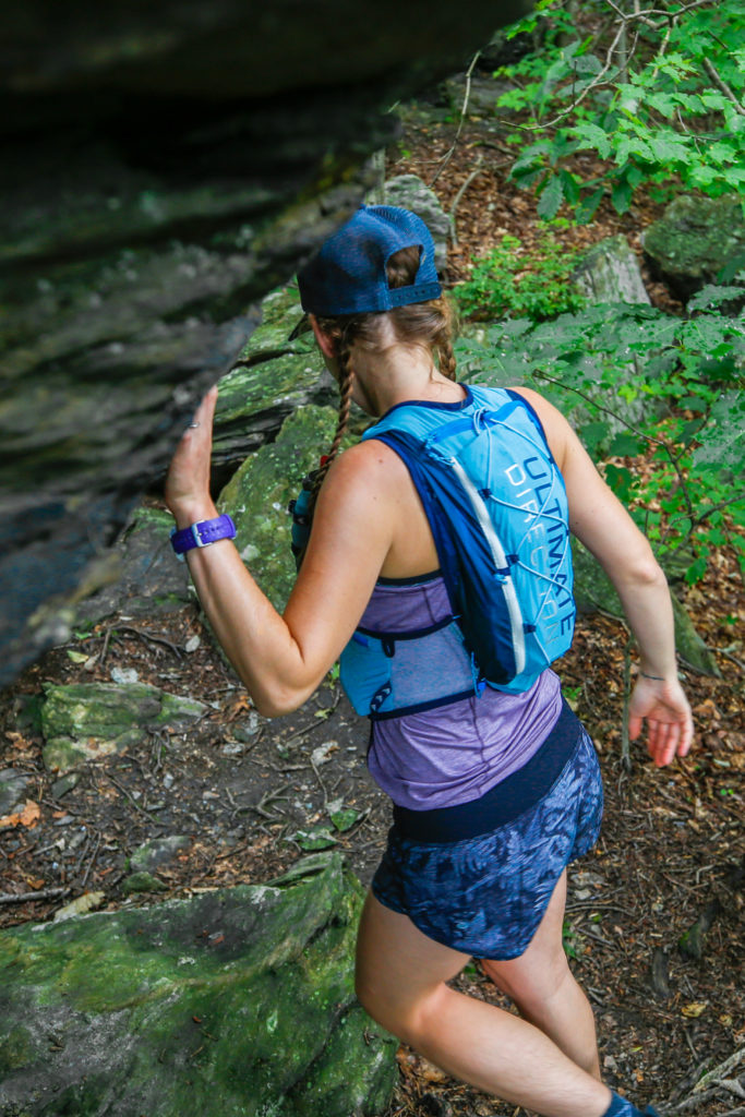 Female runner in forest wearing hydration vest