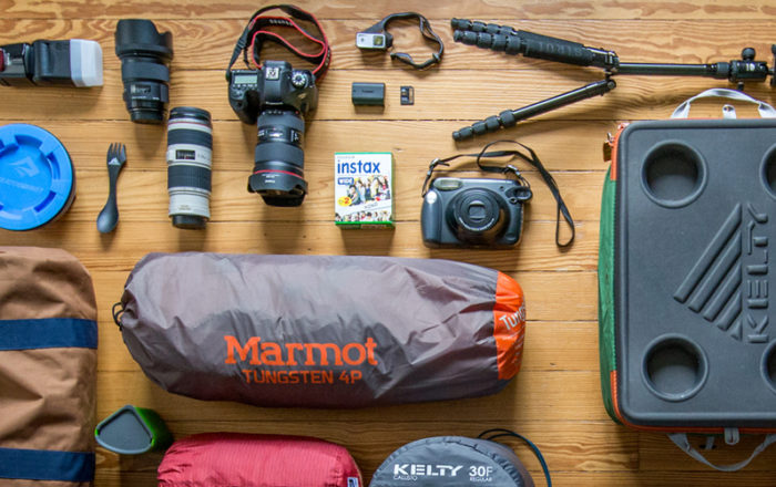 Camping gear on wooden background, including Marmot tent, Kelty cooler and sleeping bag, Gregory pack, Helinox chair and Sea to Summit dish.