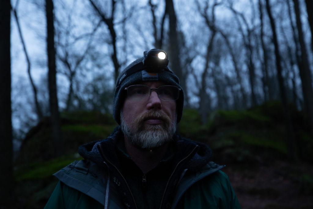 Troy in dark forest wearing headlamp