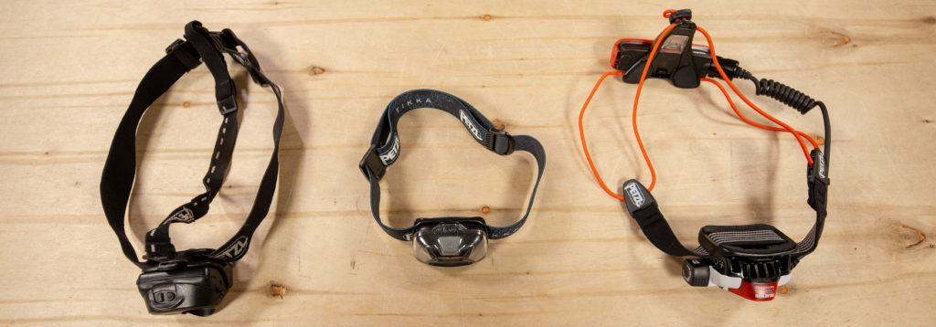 Three headlamps with different straps on a wooden surface