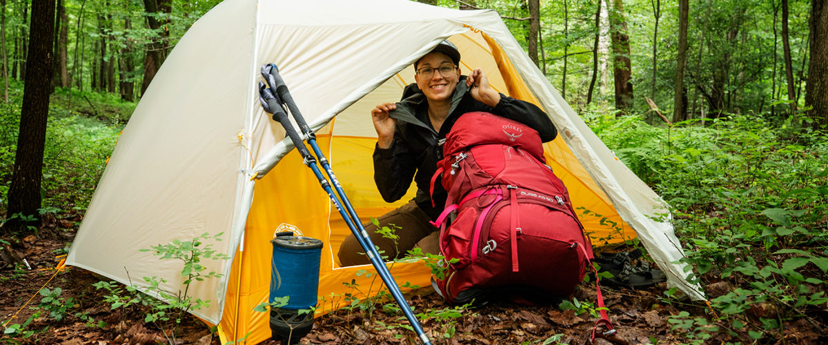 Becky in forest with giveaway gear: Big Agnes tent, Osprey pack, Outdoor Research jacket, Leki trekking poles, and JetBoil stove.