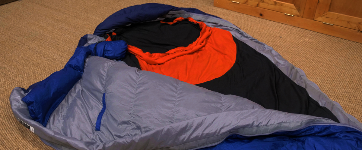 Blue sleeping bag with red and black liner inside