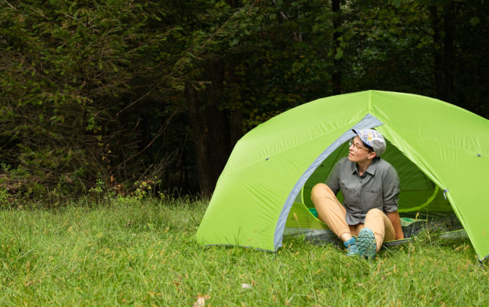 Becky in green backpacking tent in forest clearing