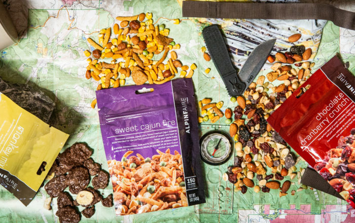 Packages of Alpen Aire trail mix on map near pack, knife, comparss and thermos