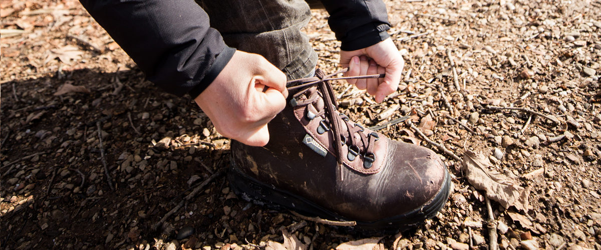 Hiker tying the laces of Vasque backpacking boot