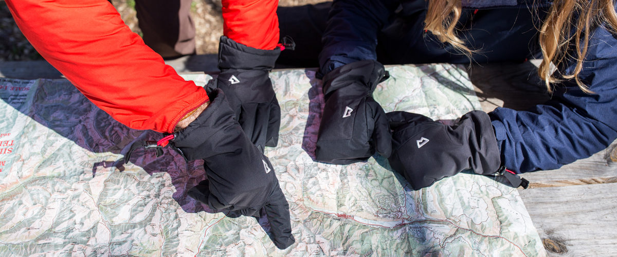 Hikers overlooking map on table, wearing gloves and mittens