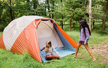 Two women camping with an orange tent