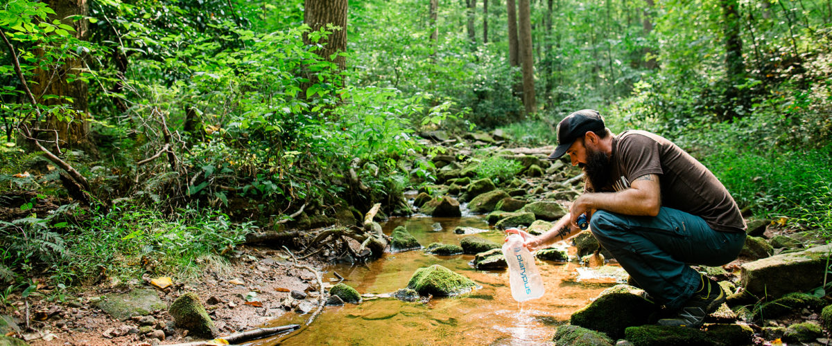 Hiker filtering drinking water with Platypus Quickdraw Microfilter water treatment System